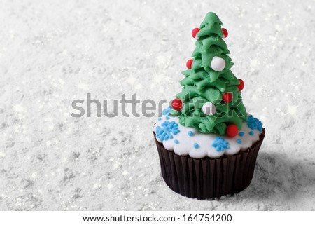 Cupcake Christmas tree on white snow. Merry Christmas - stock photo