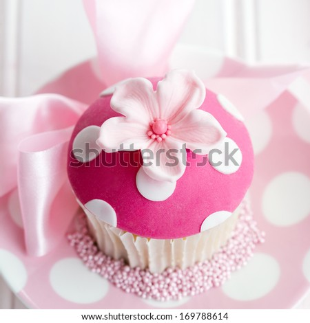 Cupcake decorated with a pink fondant flower - stock photo
