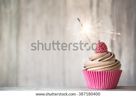 Cupcake decorated with chocolate buttercream and a sparkler - stock photo