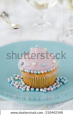 Cupcake decorated with cream and sugar pearls on plate - stock photo