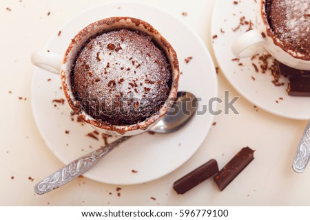 Cupcake in a mug on a white background. Home-made fast baking. Cupcakes with sugar powder and chocolate