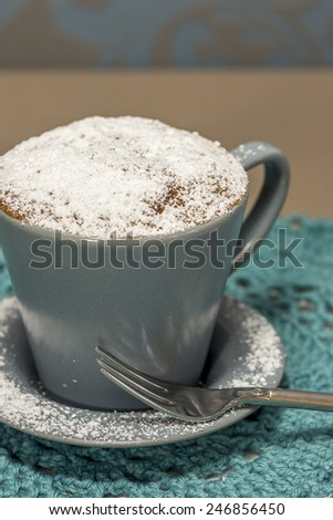 cupcake made in a coffee cup, with powdered sugar - stock photo