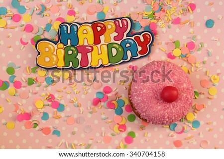 Cupcake on pink confetti polka dot background - happy birthday card - stock photo