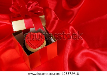 Cupcake with a red heart on top in gifts boxes on red satin background