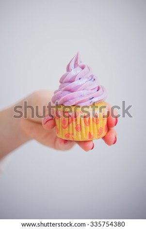 cupcake with blueberry cream in the hand - stock photo