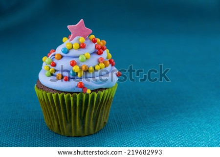 cupcake with blueberry frosting  colorful sprinkles Isolated on blue.