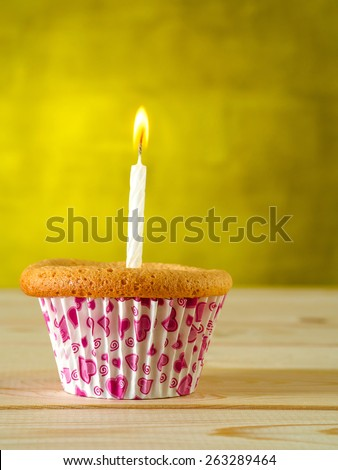 Cupcake with burning candle - stock photo