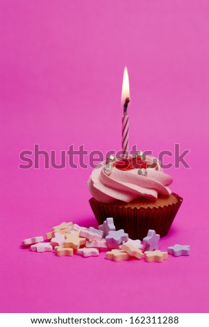 Cupcake with candle on the pink background