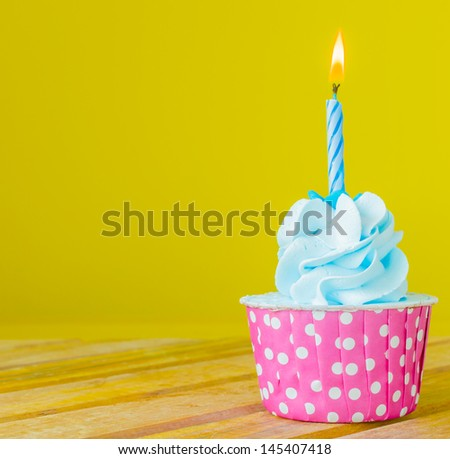 Cupcake with candle on top on color background - stock photo