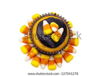 Cupcake with candy corn and chocolate cream displayed on white background. - stock photo