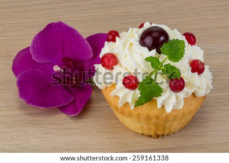 Cupcake with cherry and mint served orchid flower - stock photo