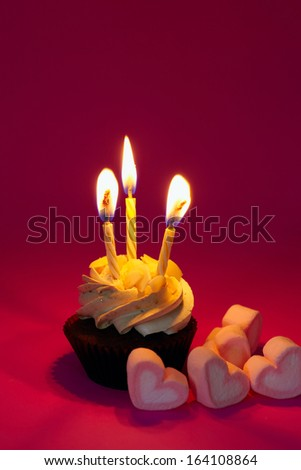 Cupcake with cream and lighting candles with candys on red - stock photo