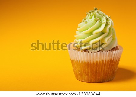 cupcake with cream isolated on orange background with copyspace