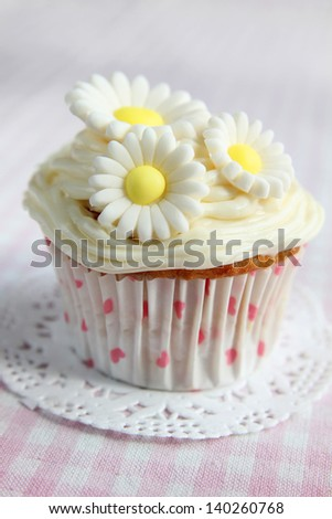 Cupcake with daisy on top on a  pink and white checkered tablecloth - stock photo