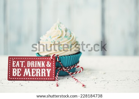 """Cupcake with """"Eat, drink and be merry"""" sign - stock photo"""