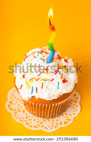 Cupcake with one burning candle on yellow napkin