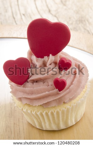cupcake with pink butter cream and red hearts