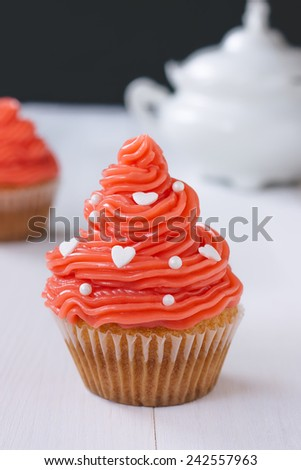 Cupcake with pink buttercream on a white wooden table