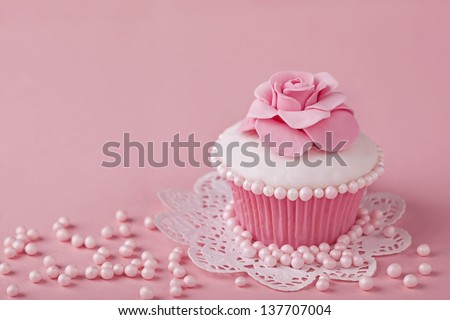 Cupcake with pink flowers on a stand - stock photo