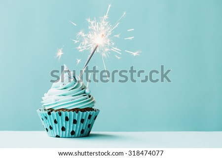 Cupcake with sparkler against blue