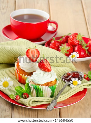 Cupcake with strawberry on a wooden table. Selective focus