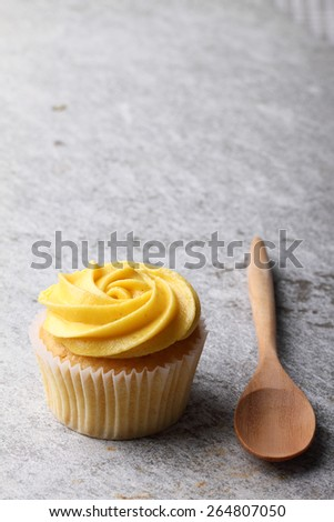 cupcake with swirl frosting with wooden spoon - stock photo