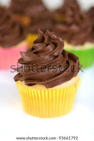 cupcake with swirled chocolate frosting in yellow wrapper - stock photo