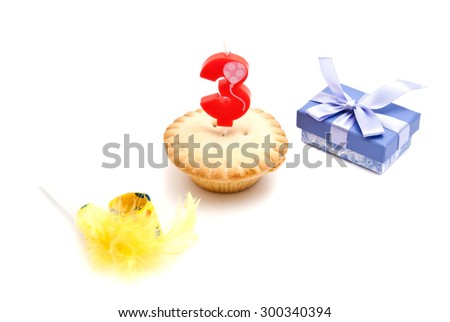 cupcake with three years birthday candle, gift and whistle on white background - stock photo