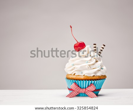 Cupcake with vanilla buttercream icing and a cherry on top. - stock photo