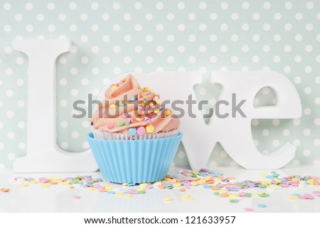 cupcake with whipped cream in a blue love setting