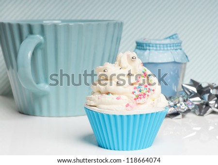 cupcake with whipped cream swirl in blue setting - stock photo