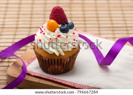 Cupcake with white cream decorated with strawberry and blueberry on wooden background