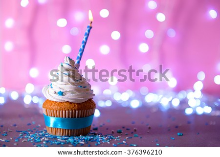 Cupcake with white cream icing and candle on a glitter background - stock photo