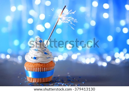 Cupcake with white cream icing and sparkler on a glitter background - stock photo