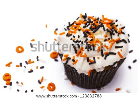 Cupcake with white icing decorated with sprinkles on white background. - stock photo