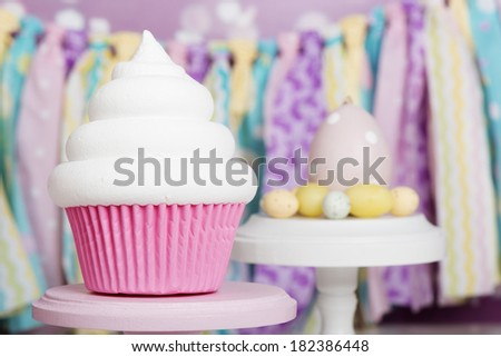 Cupcake with white swirl in pink liner and easter eggs - stock photo