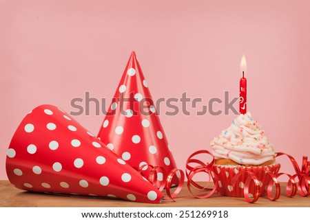 cupcakes and red party hat on a pink background - stock photo
