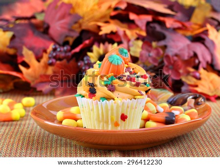 Cupcakes decorated for fall or Halloween on a pumpkin plate.  Festive sprinkles top the cupcakes and candies and leaves complete the autumn scene.