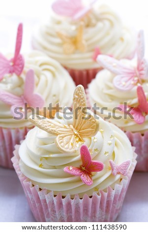 Cupcakes decorated with pink and gold fondant butterflies - stock photo