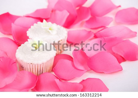 Cupcakes, muffins with white icing on white table with rose petals - stock photo