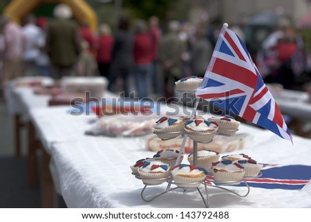 Cupcakes sat on a table decorated with the Union Jack flag.