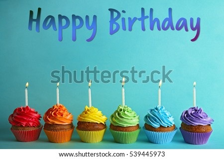 Cupcakes with candles and text HAPPY BIRTHDAY on color background