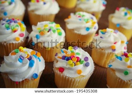 Cupcakes with colorful sprinkles on a wooden table - stock photo