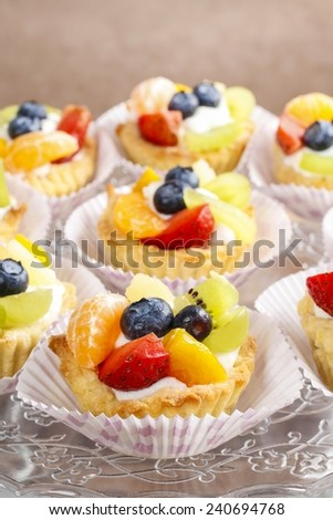 Cupcakes with cram and fresh fruits: strawberry, peach, kiwi, blueberry - stock photo