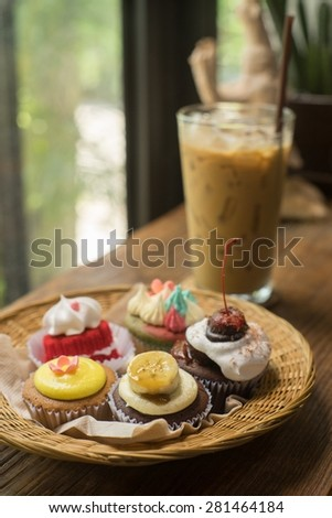Cupcakes with iced latte on old wooden table. - stock photo