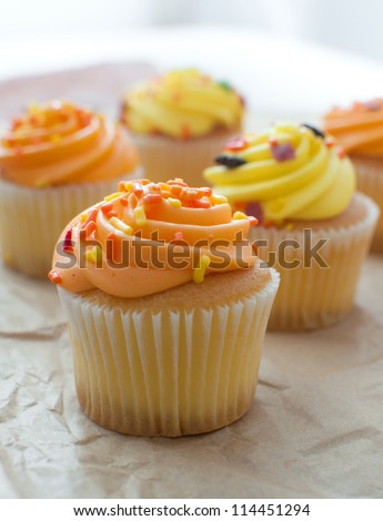Cupcakes with orange and yellow frosting vertical - stock photo