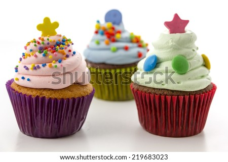 cupcakes with pink and green cream isolated and sprinkles on white background