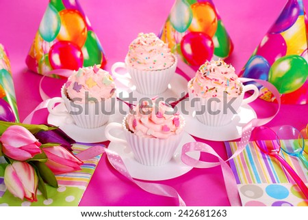 cupcakes with pink cream and sugar sprinkles in white tea cup shape molds for birthday party