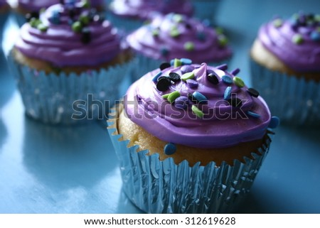 Cupcakes with purple frosting and sprinkles - stock photo