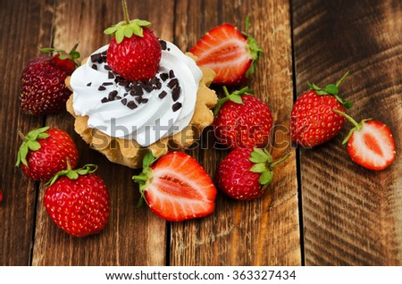 Cupcakes with strawberries and cream, fresh organic strawberries on wooden background  - stock photo